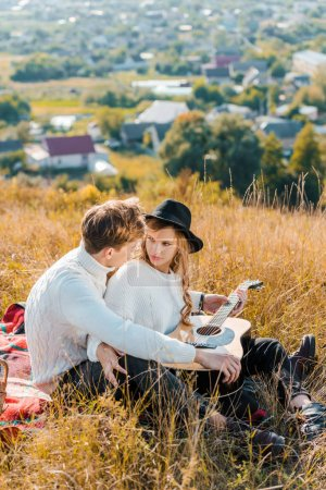 smiling couple resting on meadow while young man holding guitar