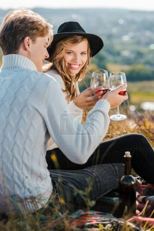happy couple clinking with wineglasses during picnic on meadow