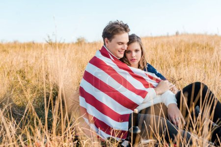 smiling couple with american flag relaxing on rural meadow, independence day concept