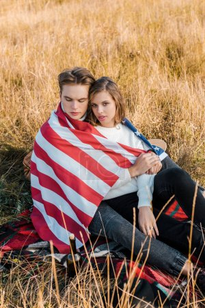 young couple with american flag resting on plaid, independence day concept