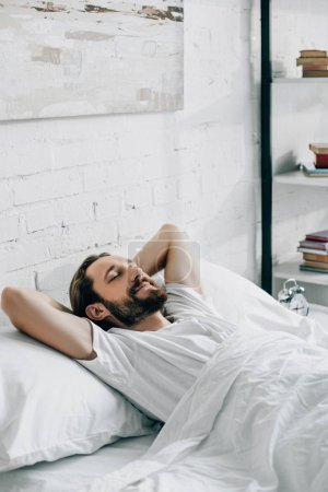 smiling young bearded man waking up in bedroom at home