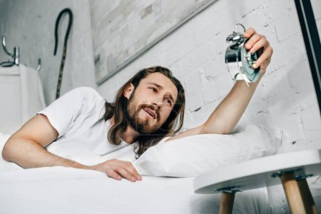 selective focus of Jesus turning off alarm clock in bed at home
