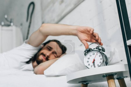 selective focus of upset Jesus turning off alarm clock during morning time in bedroom at home