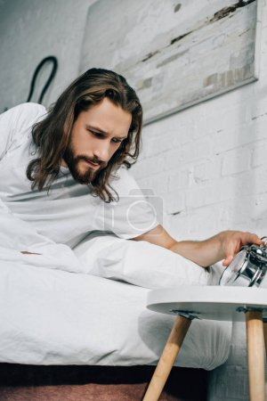 young long haired man turning off alarm clock in bedroom at home