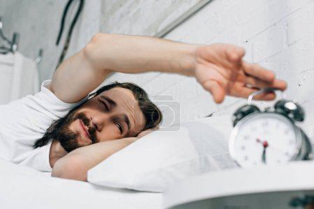 selective focus of Jesus turning off alarm clock during morning time in bedroom at home