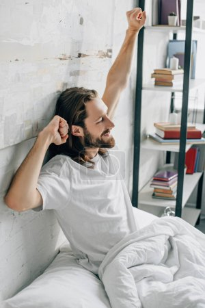 side view of young bearded man with long hair doing stretch during morning time in bed at home