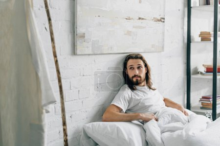selective focus of Jesus waking up in bed and looking at own robe and wooden staff at home