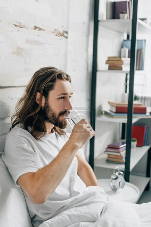 side view of young bearded man with long hair having headache and taking pill with glass of water in bedroom at home