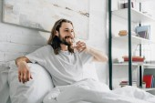 smiling bearded man with long hair drinking water in bedroom at home