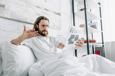 angry bearded businessman with long hair reading newspaper and gesturing by hand in bed during morning time at home