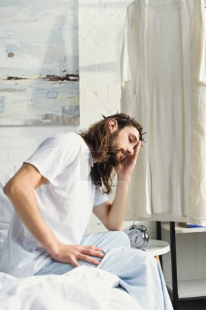 selective focus of upset Jesus sitting on bed during morning time in bedroom at home
