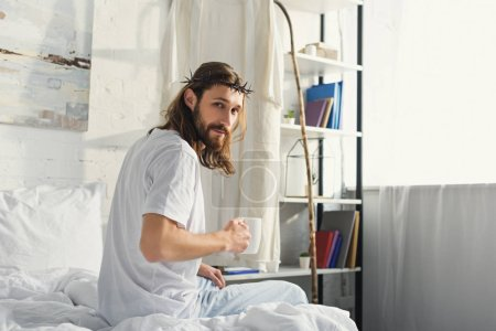 selective focus of Jesus in crown of thorns looking at camera and holding coffee cup in bedroom during morning time at home