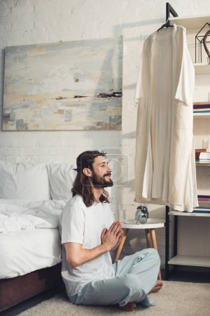 happy Jesus in crown of thorns sitting on floor in lotus position during morning time at home