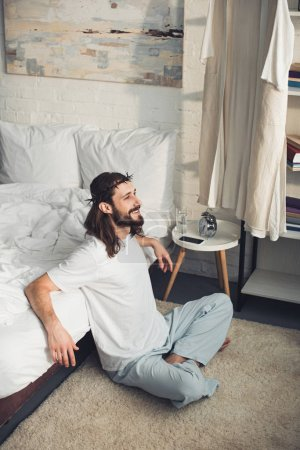 high angle view of smiling Jesus sitting on floor near bed during morning time in bedroom at home