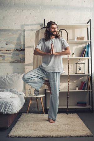 smiling Jesus in crown of thorns standing in tree pose in bedroom at home