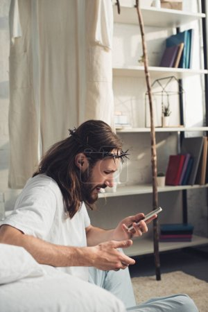 side view of Jesus in crown of thorns using smartphone in bedroom at home