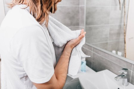 cropped image of Jesus with towel over shoulder wiping hands in bathroom