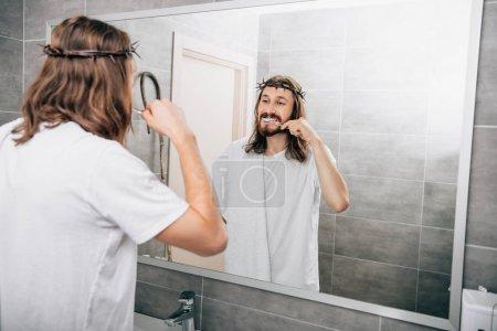 rear view of Jesus with towel over shoulder brushing teeth in bathroom