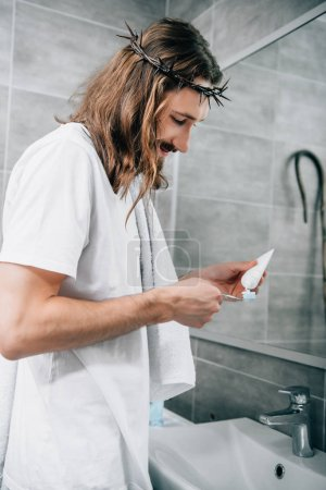 side view of Jesus in crown of thorns putting toothpaste on brush in bathroom