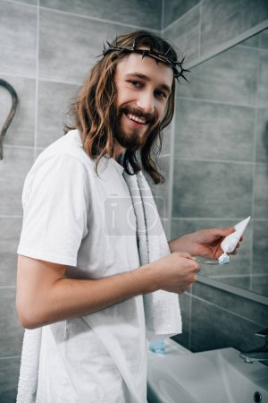happy Jesus in crown of thorns looking at camera and putting toothpaste on brush in bathroom