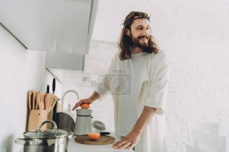 happy Jesus looking away and doing orange juice by juicer in kitchen at home