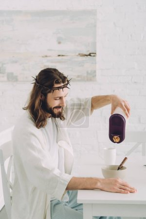 cheerful Jesus pouring cornflakes into bowl at table in kitchen at home