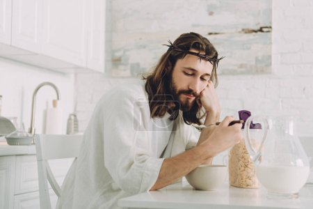 tired Jesus eating corn flakes on breakfast in kitchen at home