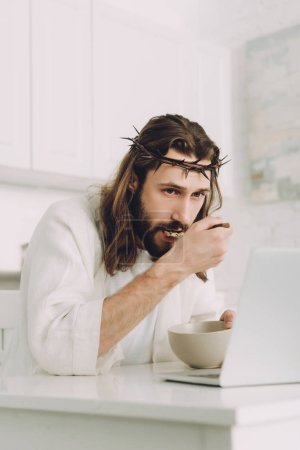 selective focus of Jesus eating corn flakes on breakfast at table with laptop in kitchen at home