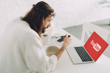 Photo for Side view of Jesus eating corn flakes on breakfast at table with laptop with youtube webiste on screen at home - Royalty Free Image