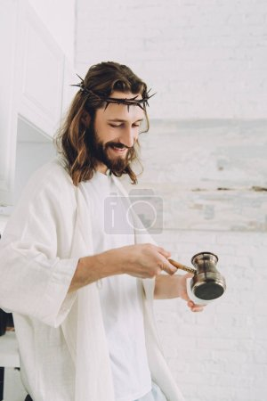 Photo for Smiling Jesus pouring coffee from cezve into cup in kitchen during morning time at home - Royalty Free Image