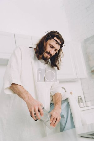 low angle view of Jesus grinding coffee beans with hands in manual coffeemill in kitchen at home