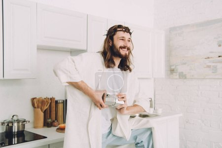 smiling Jesus grinding coffee beans with hands in manual coffeemill in kitchen at home