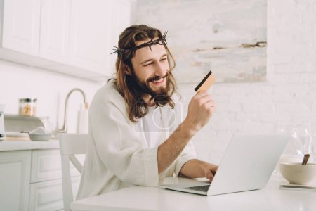smiling Jesus holding credit card and doing online shopping at table with laptop in kitchen at home