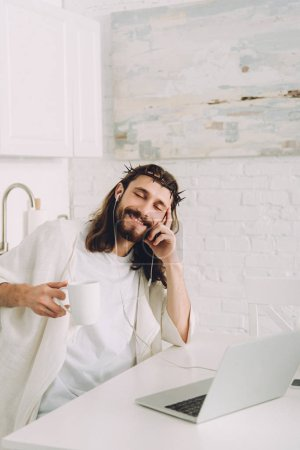 cheerful Jesus in earphones listening music and holding cup of coffee at table with laptop in kitchen at home