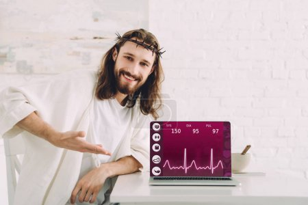 happy Jesus in crown of thorns pointing at laptop with medical application on screen in kitchen at home