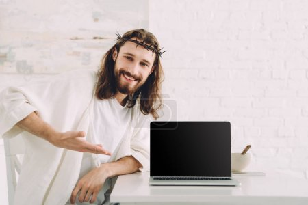 smiling Jesus in crown of thorns pointing at laptop with blank screen in kitchen at home