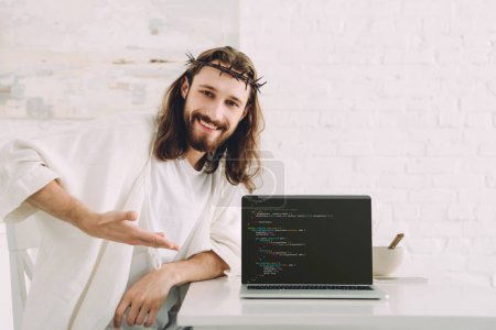 happy Jesus holding cup of coffee and pointing at laptop with html code in kitchen at home