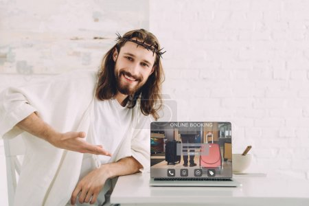 smiling Jesus in crown of thorns pointing at laptop with online booking website in kitchen at home