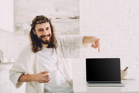 happy Jesus holding cup of coffee and pointing at laptop with blank screen in kitchen at home