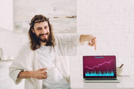 smiling Jesus holding cup of coffee and pointing at laptop with trading on screen in kitchen at home