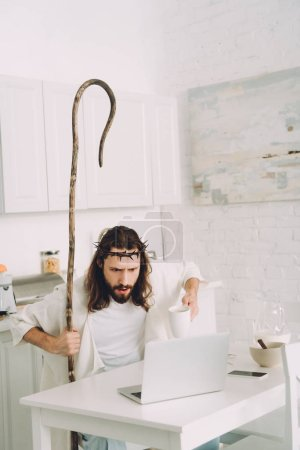 shocked Jesus with coffee cup and wooden staff looking at laptop in kitchen at home