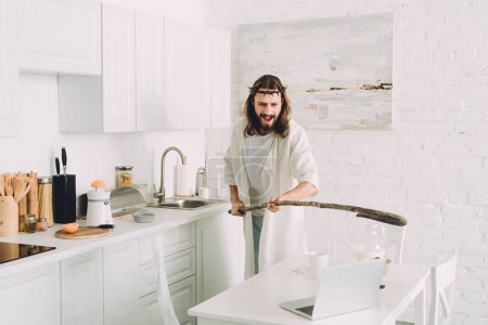 aggressive Jesus hitting laptop by wooden staff in kitchen at home