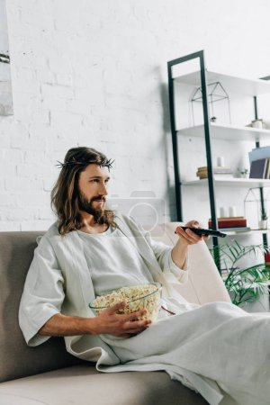 serious Jesus in crown of thorns watching tv and sitting with bowl of popcorn on sofa at home