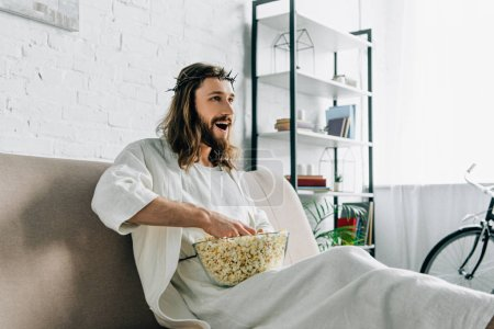 cheerful Jesus in crown of thorns watching tv and sitting with bowl of popcorn on sofa at home