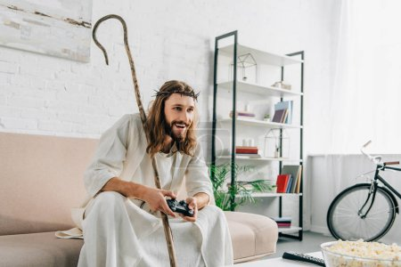 happy Jesus with wooden staff playing video game by joystick on sofa at home