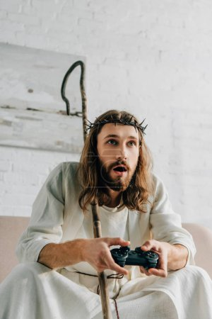 emotional Jesus with wooden staff playing video game by joystick on sofa at home