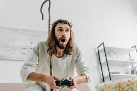 shocked Jesus with wooden staff playing video game by joystick on sofa at home