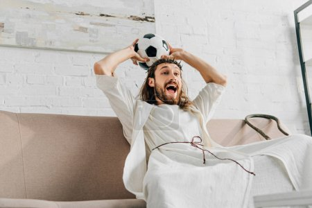 excited Jesus in crown of thorns holding soccer ball above head and watching football match at home
