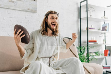 excited Jesus in crown of thorns gesturing by hand and watching american football on sofa at home