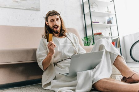 happy Jesus showing credit card, winking and doing online shopping on laptop near sofa at home